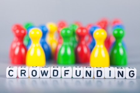 Cube Letters show crowdfunding  in front of unsharp ludo figures. Background is light gray Stock Photo