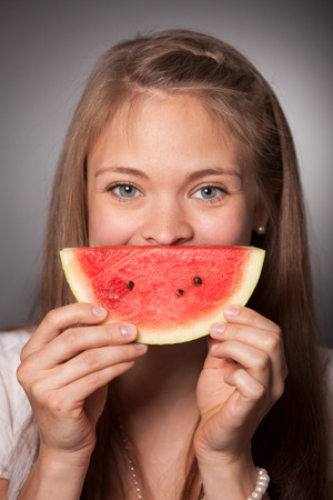 A beautiful young Women hold a slice of a melon in front of her Face.She is smiling. photo