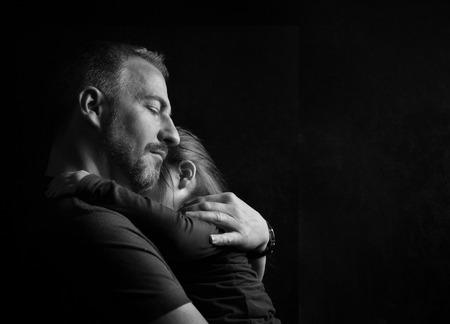 ni�o durmiendo: Tocar fieltro del coraz�n Negro Imagen blanco y del padre con la hija Ojos cerrados joven abrazando tiernamente con el fondo oscuro con el espacio de la copia Foto de archivo