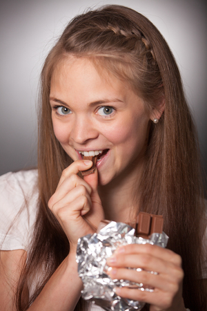 long haired: Close up Smiling Young Long Haired Woman Eating Chocolate Bar in Foil While Looking at the Camera on a Gray Gradient Background. Stock Photo