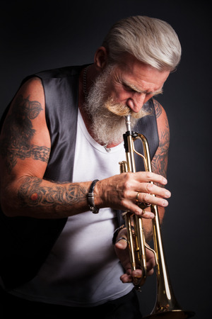 trumpet player: PIcture of a white haired trumpet player with a long white beard. Stock Photo