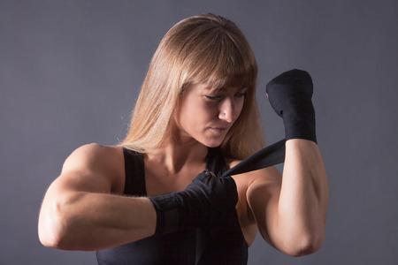 mujeres fitness: Aptitud de las mujeres rubias applys vendajes para el boxeo.