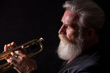 profile picture: PIcture of a white haired trumpet player with a long white beard. Profile picture with side light.
