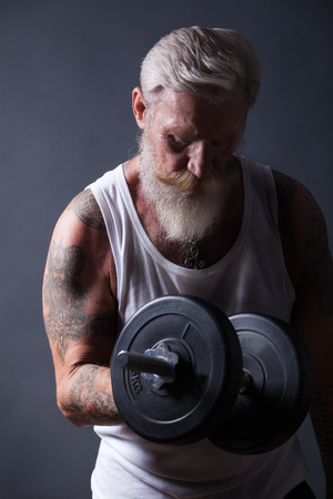 heavy weight: A beard man with a white beard make a workout with a dumbbell Stock Photo