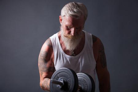 an elderly person: Hombre mayor con larga barba blanca y una camiseta blanca hace un entrenamiento con una mancuerna. Foto de archivo