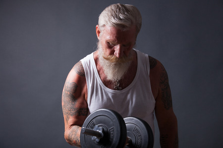 muskeltraining: Senior man with long white beard and a white t-shirt makes a workout with a dumbbell. Lizenzfreie Bilder