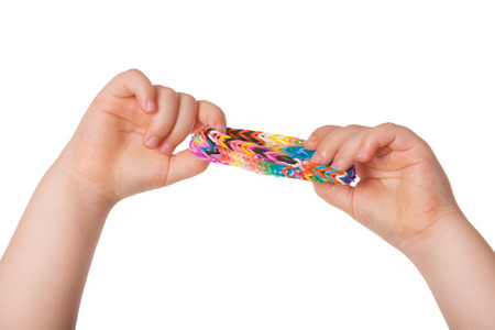 braclets: Child is holding some Loom braclets in her two hands.