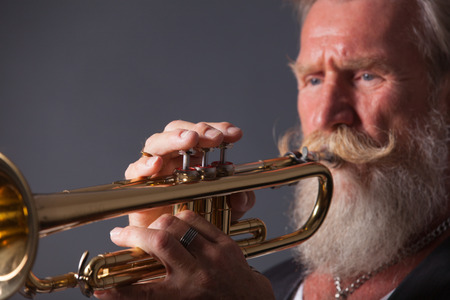 trumpet player: PIcture of a white haired trumpet player with a long white beard. Profile picture with side light.