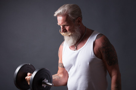 attractive people: Senior man with long white beard and a white t-shirt makes a workout with a dumbbell. Stock Photo