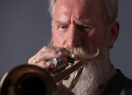 trumpet player: PIcture of a white haired trumpet player with a long white beard.Front picture with side light.