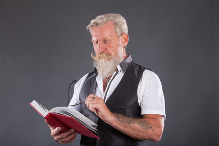 Cool senior man is reading a book on a table . The beard man is wearing a waistcoat and glasses. Stock Photo