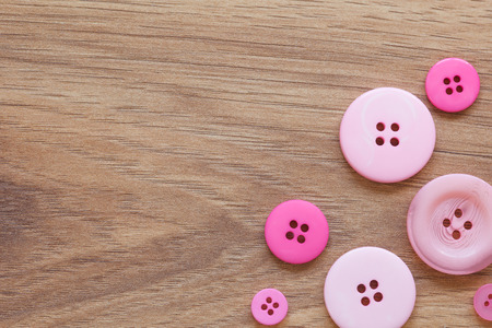 sewing item: A lot of different buttons in pink and purple laying on wood . Copyspace on the wood. Stock Photo