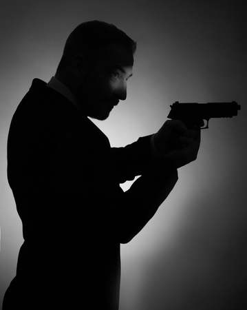shadow silhouette: A shadow picture of a man with a smoking and a gun. Black and white picture. Stock Photo