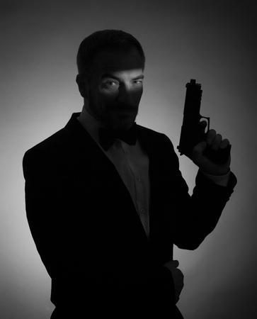 mujer con pistola: Un cuadro sombra de un hombre con un fumador y un arma. En blanco y negro foto.
