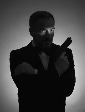 special agent: A shadow picture of a man with a smoking and a gun. Black and white picture. Stock Photo