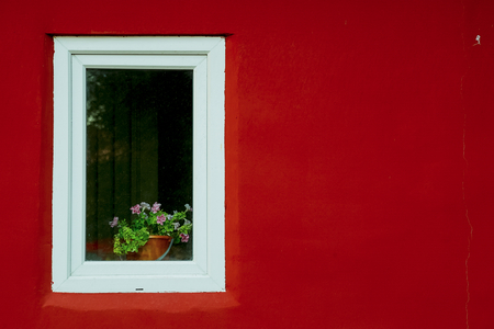 view to outside: White window on a red wall on the street.