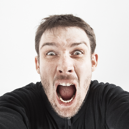 bawl: unshaven man in a black jacket on a white background shouts.
