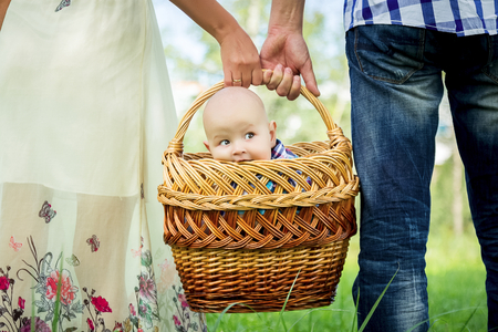 nursling: Man and woman holding basket with little boy.