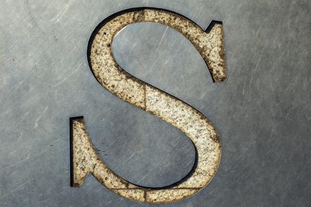 metal sheet: letter S cut in the metal sheet. Stock Photo