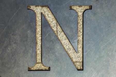 n: letter N cut in the metal sheet.