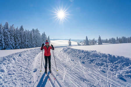 beautiful active senior woman cross-country skiing in fresh fallen powder snow in the Allgau alps near Immenstadt, Bavaria, Germany Stockfoto
