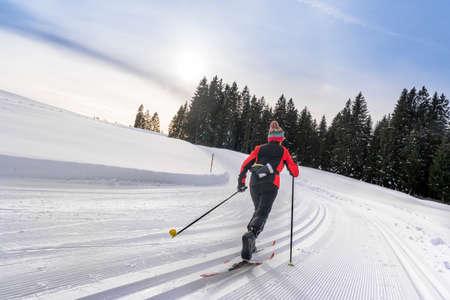 beautiful active senior woman cross-country skiing in fresh fallen powder snow in the Allgau alps near Immenstadt, Bavaria, Germany Foto de archivo