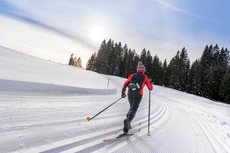 beautiful active senior woman cross-country skiing in fresh fallen powder snow in the Allgau alps near Immenstadt, Bavaria, Germany Stock Photo
