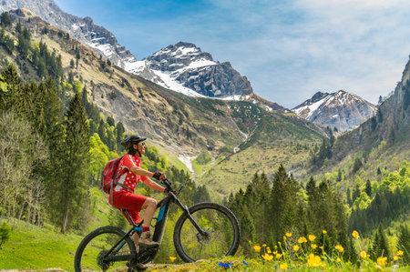 pretty senior woman riding her electric mountain bike the Oy Tal Valley near Oberstdorf, Allgau Alps, Bavaria, Germany