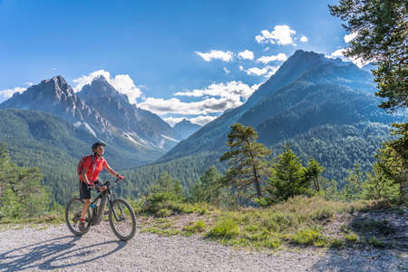 nice and active senior woman riding her electric mountain bike on a old military road from Toblach upt to the summit of Marchkinkele eith spectacular view to the Three peaks of Lavaredo, South Tirol,