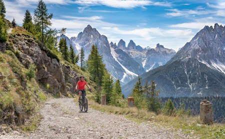 nice and active senior woman riding her electric mountain bike on a old military road from Toblach upt to the summit of Marchkinkele eith spectacular view to the Three peaks of Lavaredo, South Tirol, Stock fotó