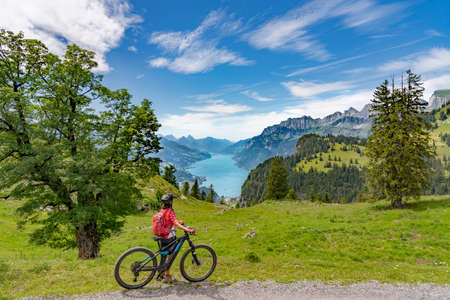 active woman riding her electric mountain bike below the seven summits of Churfirsten, enjoying the awesome view down to Lake Walensee Canton St. Gallen, Switzerland
