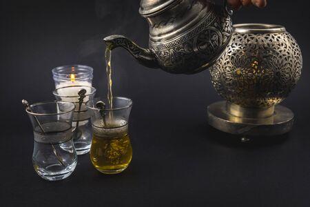 Serving green Moorish tea from the top of a metal cup to three glasses, cup and Turkish basses on a black background