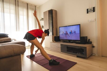 A young Caucasian woman doing exercises in the room following the instructions of the online teacher. Sport in the covid19 quarantine at home