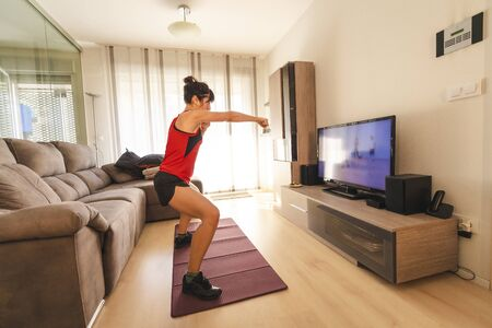 A young brunette woman punching the air in her living room at the covid19 quarantine, kick boxing exercises
