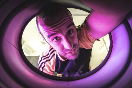 Am I escaping from quarantine through this hole? Photo inside a washing machine Stockfoto