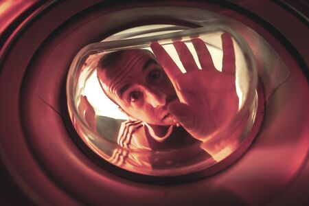 Is there life in this world? A young man looking out the window of a ship with a red light. Photo inside a washing machine