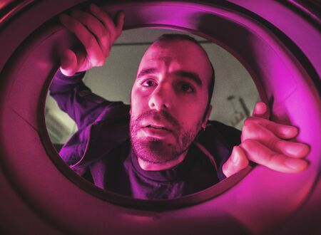Interior of a washing machine photo of a young Caucasian man, with dark blue and red lights