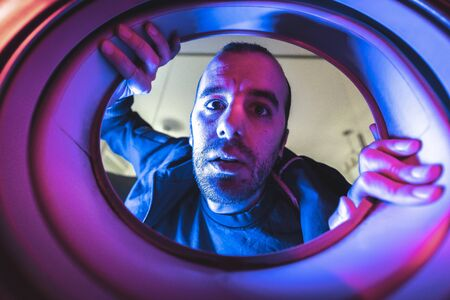 Portrait from inside a washing machine of a young caucasian man, with blue and red lights and in the dark