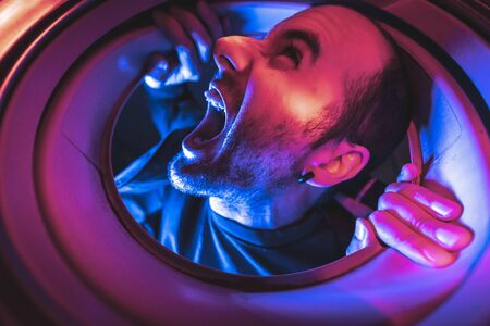 Portrait from inside a washing machine of a young caucasian man screaming, with lights and in the dark