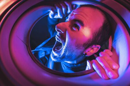 Portrait from inside a washing machine of a young caucasian man screaming