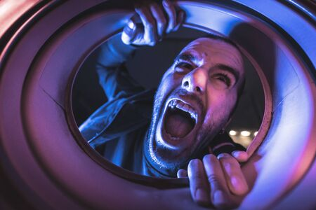 Portrait from inside a washing machine of an angry young Caucasian man Stockfoto