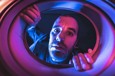 Portrait from inside a washing machine of a scared young Caucasian man Stockfoto