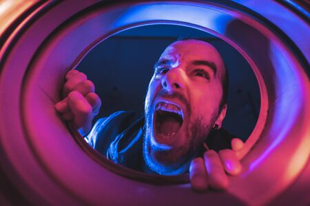 Portrait from inside a washing machine of a young Caucasian man who wants to escape