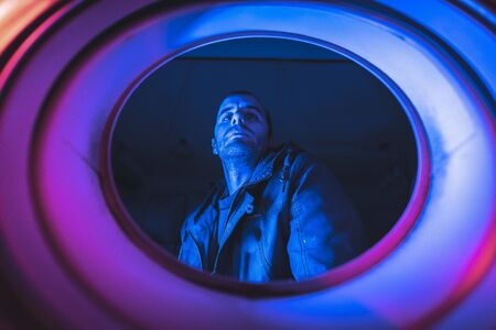 Portrait from inside a washing machine of a young Caucasian man