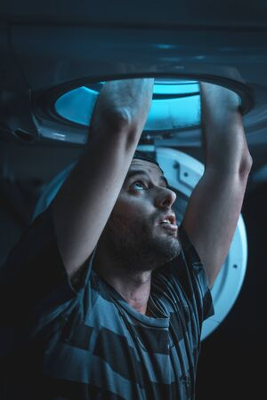 A young man with a back hat facing his nightmares. spaceship simulation