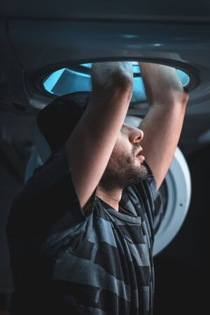 A young man getting into the washing machine pretending to be a space ship, vertical photo