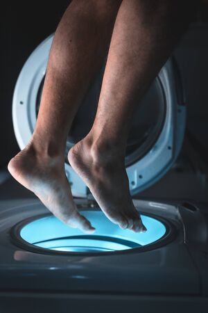 Feet of a young man getting into the washing machine pretending to be a space ship Stockfoto