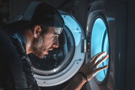 A young man in front of the light coming out of the washing machine, simulating a ship