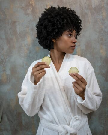 Girl with afro hair in white coat in a cosmetic center with cucumbers