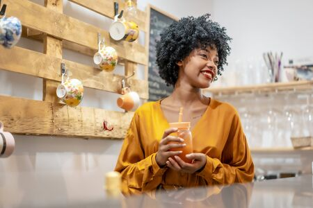 Dominican girl with afro hair drinking an orange juice Stock Photo